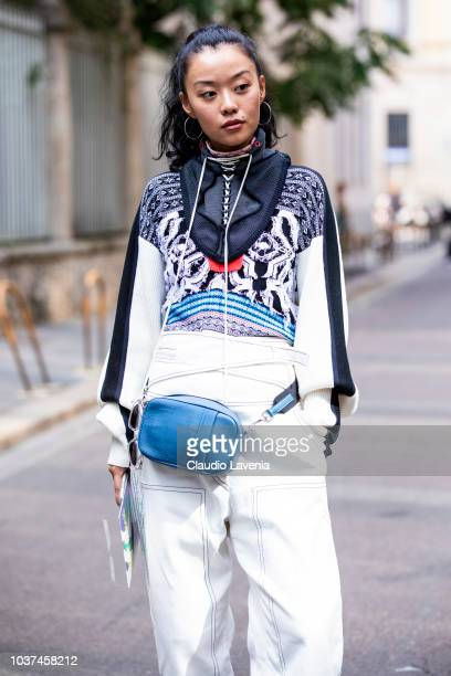 A guest wearing Sportmax black and white pullover white pants and blue belt bag is seen after the Sportmax show during Milan Fashion Week...