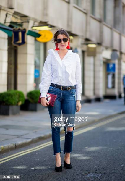 A guest wearing statement earings white blouse ripped denim jeans during the London Fashion Week Men's June 2017 collections on June 10 2017 in...