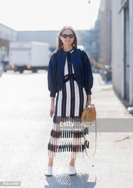 A guest wearing straw bag bomber jacket skirt outside By Malene Birger on August 09 2017 in Copenhagen Denmark