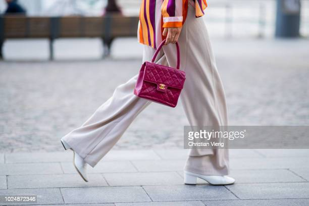 A guest wearing striped button shirt wide leg pants red Chanel bag seen during Stockholm Runway SS19 on August 28 2018 in Stockholm Sweden