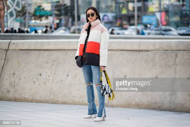 A guest wearing striped down feather jacket flared denim jeans with slit Off White bag is seen at the Hera Seoul Fashion Week 2018 F/W at Dongdaemun...