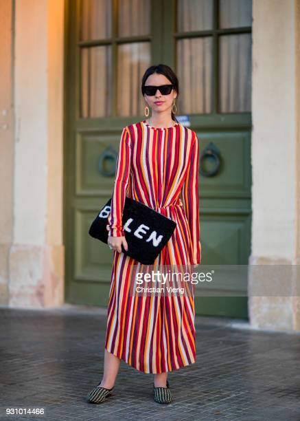A guest wearing striped dress Balenciaga clutch is seen during Tel Aviv Fashion Week on March 12 2018 in Tel Aviv Israel