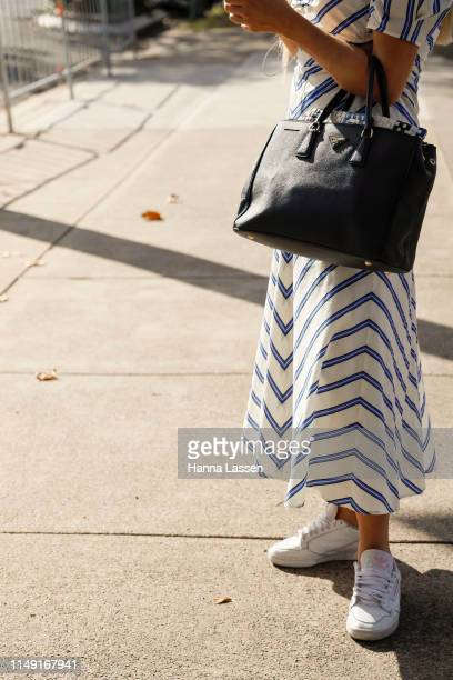 A guest wearing striped dress Prada bag and Adidas sneakers at MercedesBenz Fashion Week Resort 20 Collections on May 15 2019 in Sydney Australia