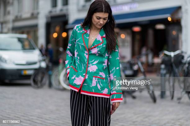 A guest wearing striped pants mint blazer jacket with floral print outside Designers Nest on August 8 2017 in Copenhagen Denmark