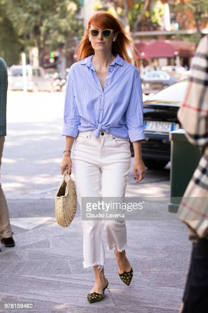 A guest wearing striped shirt and white pants is seen in the streets of Milan before the Giorgio Armani show during Milan Men's Fashion Week...