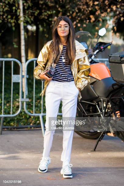 A guest wearing striped tshirt white trousers Louis Vuitton sneakers gold jacket and see trough bag is seen before the Chloe show on September 27...