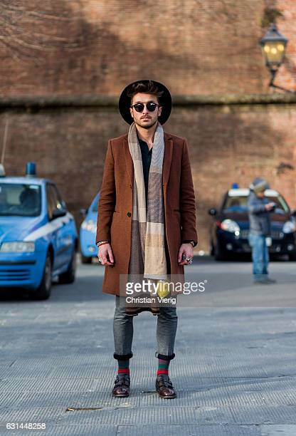 A guest wearing sunglasses scarf red brown coat skinny denim jeans socks leather shoes on January 10 2017 in Florence Italy