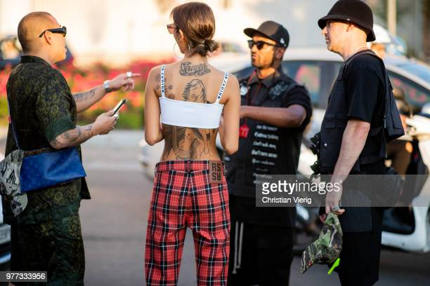 229d06649f7ce A guest wearing Supreme Louis Vuitton sunglasses white Dior cropped top red  lumberjack plaid pants is