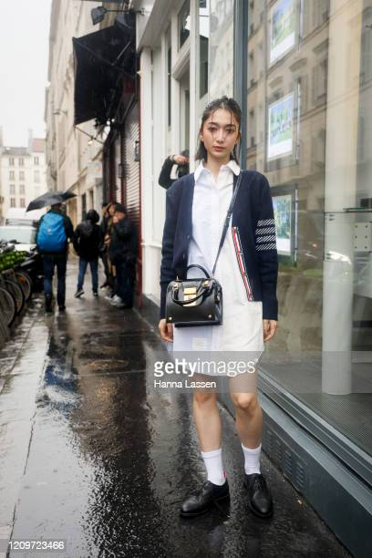 Guest wearing Thom Browne cardigan, white shirt dress, black leather bag and brogues outside Thom Browne during Paris Fashion Week Womenswear...