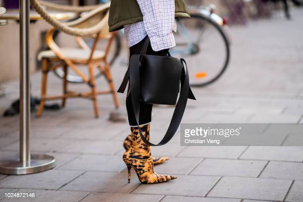 A guest wearing tiger print ankle boots black bag is seen during Stockholm Runway SS19 on August 28 2018 in Stockholm Sweden