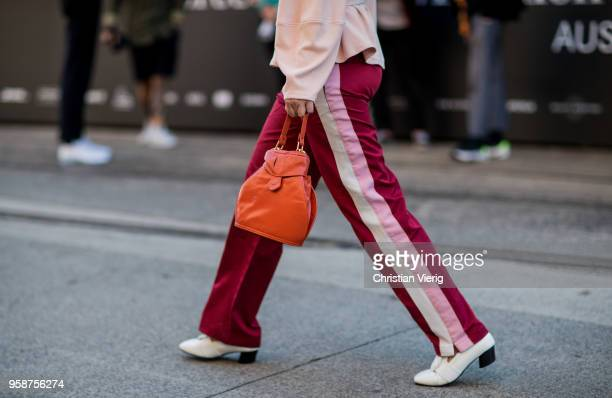 Guest wearing track suit pants with stripe, orange bag during Mercedes-Benz Fashion Week Resort 19 Collections at Carriageworks on May 15, 2018 in...
