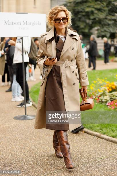 Guest wearing trench and snake skin boots outside Maison Margiela on September 25, 2019 in Paris, France.