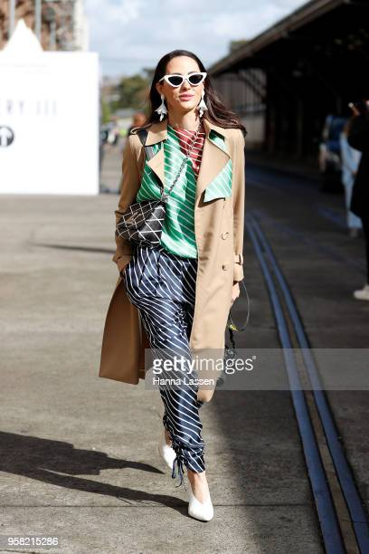 A guest wearing trench coat and Louise Vuitton bag during MercedesBenz Fashion Week Resort 19 Collections at Carriageworks on May 14 2018 in Sydney...