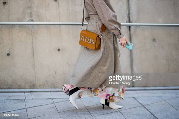 A guest wearing trench coat brown bag white ankle boots long dress with floral print is seen at the Hera Seoul Fashion Week 2018 F/W at Dongdaemun...