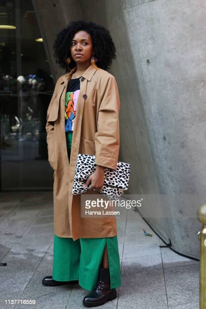 Guest wearing trench coat green wide pants and dotted clutch is seen at the Hera Seoul Fashion Week 2019 F/W at Dongdaemun Design Plaza at Dongdaemun...