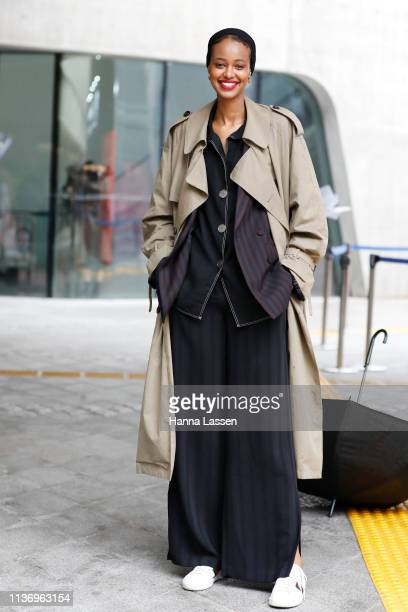 Guest wearing trench coat pajama stripe jacket and pants and Gucci sneakers is seen at the Hera Seoul Fashion Week 2019 F/W at Dongdaemun Design...