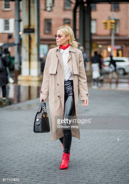 A guest wearing trench coat red ankle boots seen outside Tibi on February 11 2018 in New York City