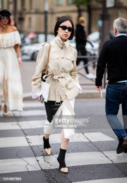 A guest wearing trench jacketis seen outside Miu Miu during Paris Fashion Week Womenswear Spring/Summer 2019 on October 2 2018 in Paris France