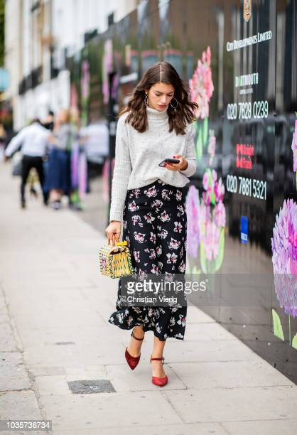 A guest wearing turtleneck knt skirt with floral print basket bag is seen outside Natasha Zinko during London Fashion Week September 2018 on...