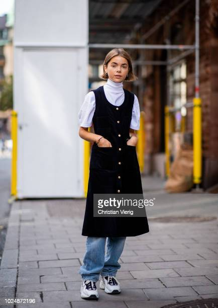 A guest wearing turtleneck shirt sleeveless dress denim jeans sneaker is seen during Stockholm Runway SS19 on August 28 2018 in Stockholm Sweden