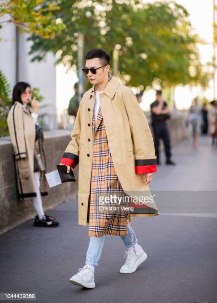 A guest wearing two trench coats beige trench coat plaid Burberry coat sneaker is seen outside Sacai during Paris Fashion Week Womenswear...