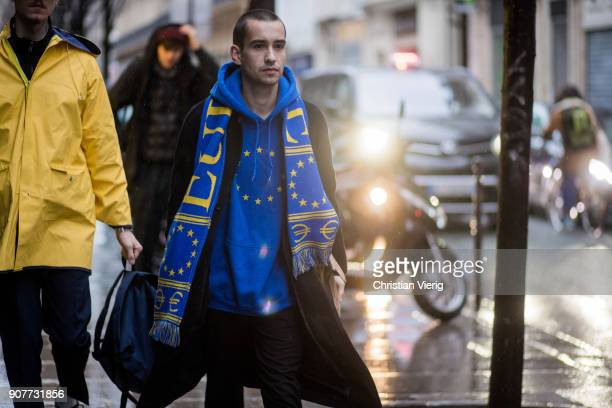 A guest wearing Vetements hoodie football scarf is seen outside Sacai on January 20 2018 in Paris France