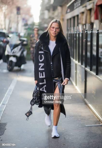 A guest wearing vinyl skirt with slit Balenciaga sneakers Balenciaga scarf is seen outside Dolce Gabbana during Milan Men's Fashion Week Fall/Winter...