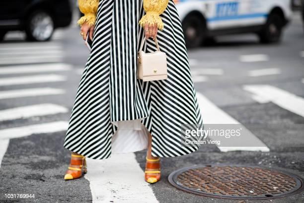A guest wearing white bag heels striped skirt yellow blouse seen outside Oscar de la Renta during New York Fashion Week Spring/Summer 2019 on...