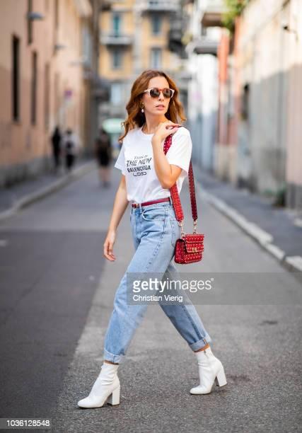 A guest wearing white Balenciaga tshirt cuffed denim boyfriends jeans white ankle boots red Valentino bag sunglasses during Milan Fashion Week...