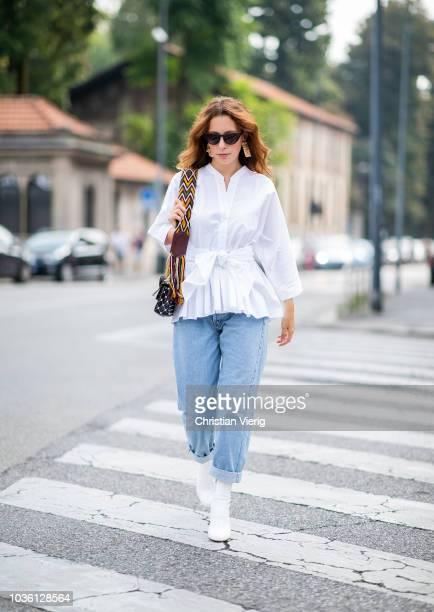 A guest wearing white blouse cuffed denim boyfriend jeans black Valentino bag sunglasses is seen during Milan Fashion Week Spring/Summer 2019 on...