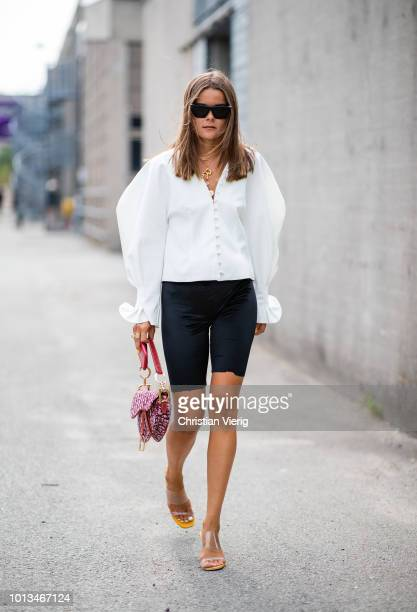Guest wearing white blouse, Dior saddle bag, cycle pants is seen outside J.Lindeberg during the Copenhagen Fashion Week Spring/Summer 2019 on August...