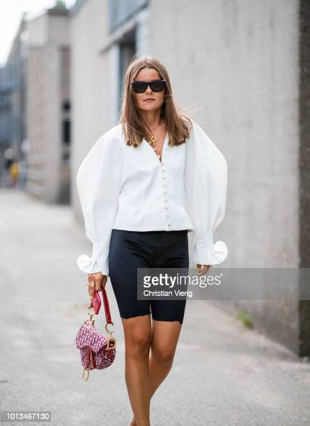 A guest wearing white blouse Dior saddle bag cycle pants is seen outside JLindeberg during the Copenhagen Fashion Week Spring/Summer 2019 on August 8...