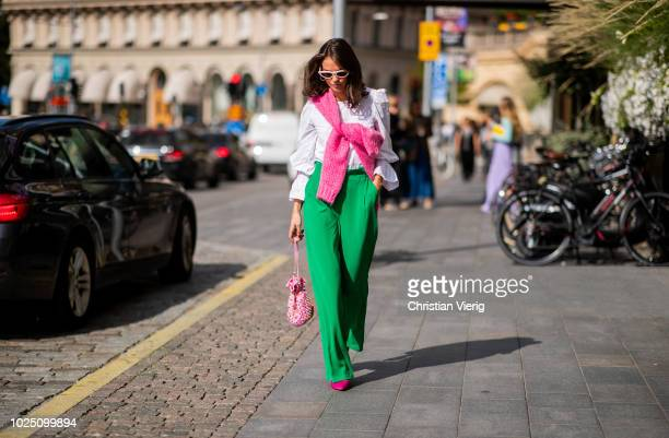 A guest wearing white blouse green pants pink bag is seen during Stockholm Runway SS19 on August 29 2018 in Stockholm Sweden
