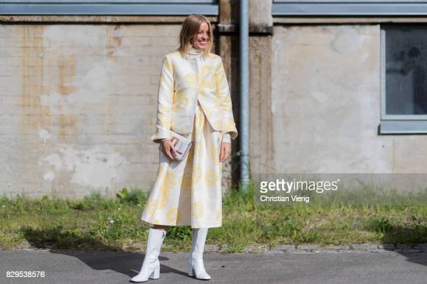 A guest wearing white boots and clutch yellow white skirt and jacket outside Ganni on August 10 2017 in Copenhagen Denmark