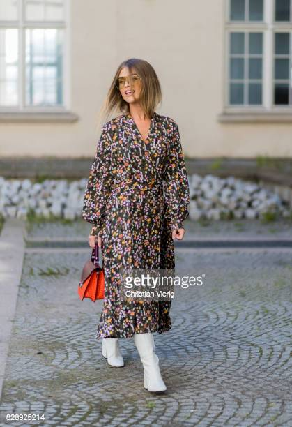 A guest wearing white boots dress with floral print outside Holzweiler on August 09 2017 in Copenhagen Denmark