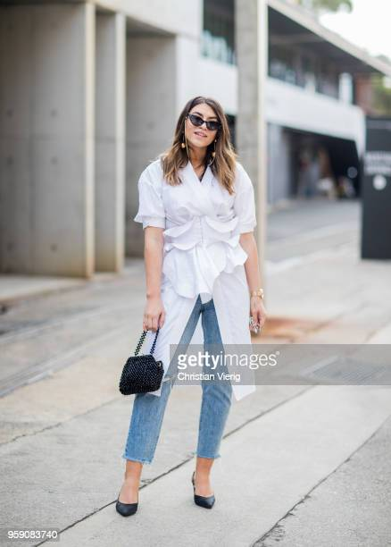 A guest wearing white button shirt with corset cropped denim jeans heels during MercedesBenz Fashion Week Resort 19 Collections at Carriageworks on...