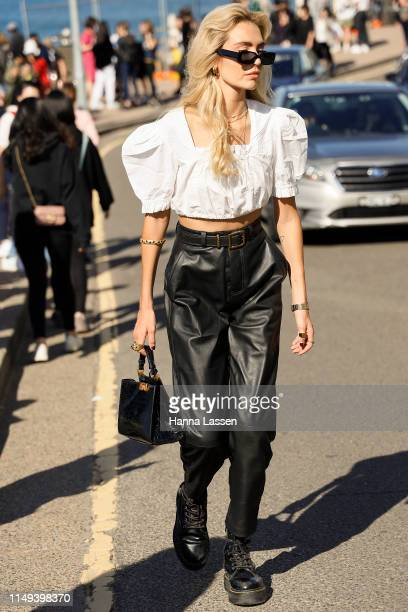 A guest wearing white cropped top black leather pants at MercedesBenz Fashion Week Resort 20 Collections on May 16 2019 in Sydney Australia