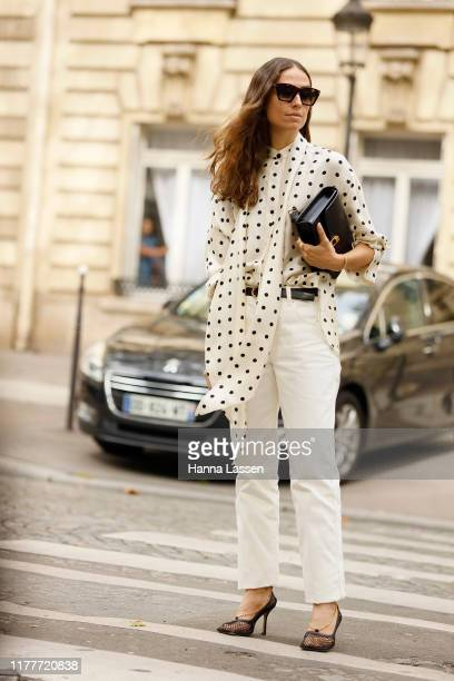 Guest wearing white dotted blouse and white jeans outside the Altuzarra show during Womenswear Spring/Summer 2020 show Paris Fashion Week on...