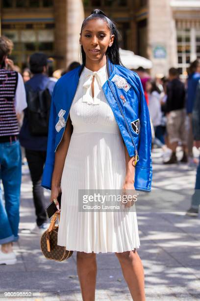 Guest wearing white dress and blue Louis Vuitton bomber jacket is seen in the streets of Paris after the Louis Vuitton show during Paris Men's...