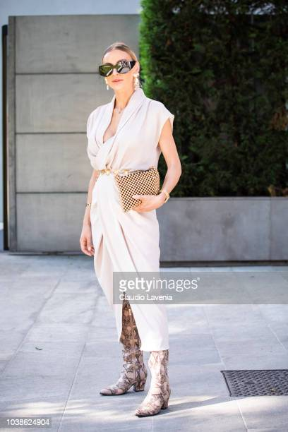 A guest wearing white dress and golden handbag is seen before the Giorgio Armani show during Milan Fashion Week Spring/Summer 2019 on September 23...