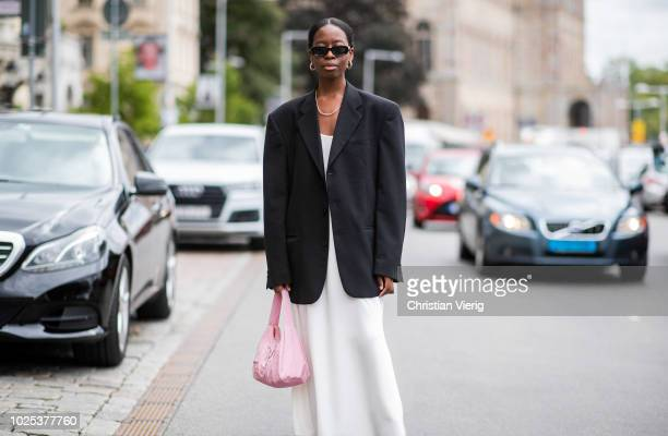 A guest wearing white dress black blazer during Stockholm Runway SS19 on August 30 2018 in Stockholm Sweden