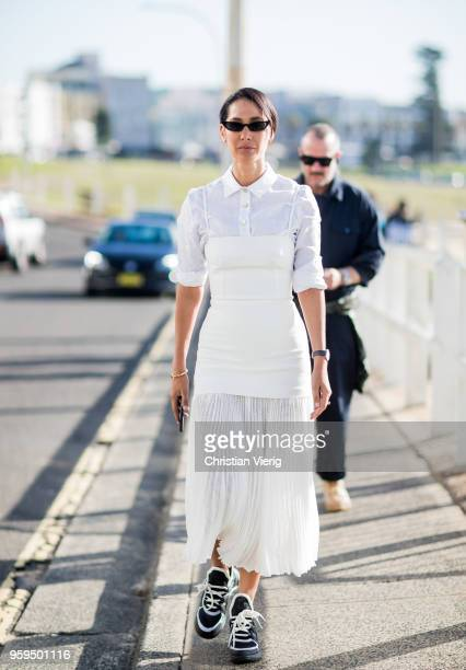 A guest wearing white dress black white sneakers during MercedesBenz Fashion Week Resort 19 Collections at Icebergs Dining Room on May 17 2018 in...