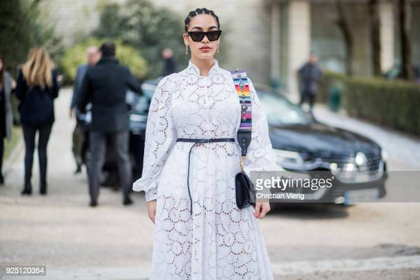 Guest wearing white dress with belt is seen outside Dior on February 27, 2018 in Paris, France.