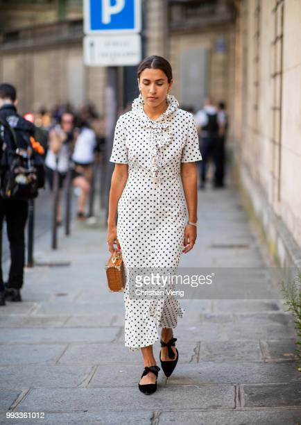 A guest wearing white dress with black dots print brown mini bag black pointed flats is seen outside Valentino on day four during Paris Fashion Week...
