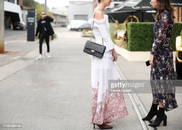 A guest wearing white maxi dress and Chanel bag at MercedesBenz Fashion Week Resort 20 Collections on May 15 2019 in Sydney Australia