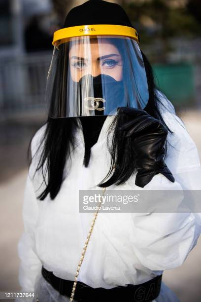 A guest wearing white nonwoven coverall Chanel mask belt and bag full of hand sanitizer is seen outside the Chanel show during Paris Fashion Week...