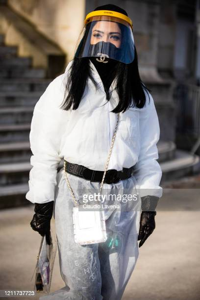 Guest, wearing white nonwoven coverall, Chanel mask, belt and bag full of hand sanitizer, is seen outside the Chanel show during Paris Fashion Week...