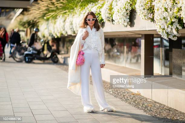 A guest wearing white pants creme white button shirt and jacket is seen during Stockholm Runway SS19 on August 28 2018 in Stockholm Sweden