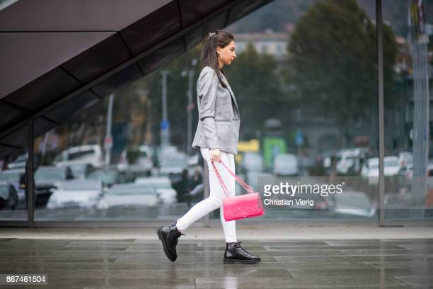 A guest wearing white pants red Valentino bag black leather shoes grey blazer jacket is seen during Tbilisi Fashion Week Spring/Summer 2018 on...