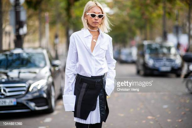 A guest wearing white pleated skirt black skirt with slit white button shirt with long sleeves white sunglasses is seen outside Sacai during Paris...